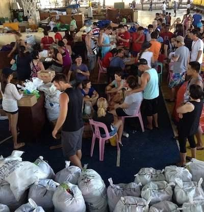 Turyści na Filipinach pomagają pakować paczki z pomocą humanitarną